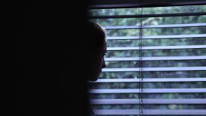 masentunut nuori ikkunan edessä