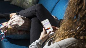 Nuori suomalainen nainen istuu sohvalla ja käyttää Snapchattia.