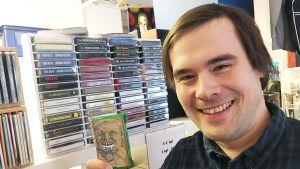 mies pitää c kasettia kädessään