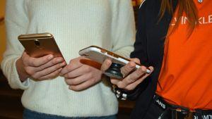 Kaksi nuorta kännyköillään.