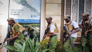Kuvassa maastopukuihin pukeutuneet ja aseistetut sotilaat etenevät rivissä hotellin seinustalla.