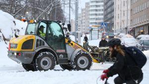 Traktori auraa tietä puhtaaksi liikenteen seassa.