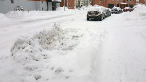Parkkipaikan ympärille kertynyt lumivalli.