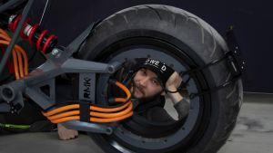 Suomalaisen sähkömoottoripyörän RMK E2:n poikkeavin piirre on vanneripustettu takapyörä. Pääsuunnittelija Teemu Saukkio kurkistaa vanteen läpi.