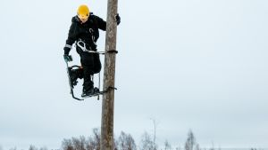 Asentaja sähköpylväässä kiipeilukengissä.