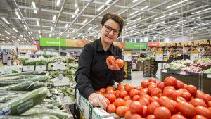 Minna Lintu poimii tomaatteja kaupassa.