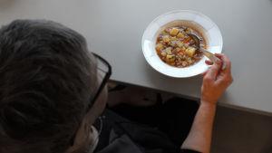 Ikääntynyt henkilö syö jauhelihakeittoa pöydän ääressä.