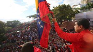 Nicolas Maduro nostaa lippua, taustalla väkijoukkoa.