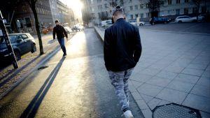 nuori poika kävelee kadulla vastavalossa