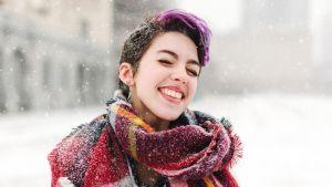 Paljaspäinen nainen lumisateessa.
