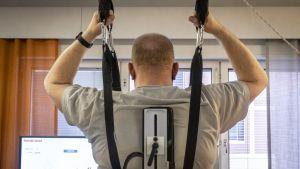 Alaraajahalvaantunut Timo Heikkinen saa apua kävelyrobotista.