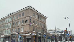 Pasaati-ostoskeskuksen vaalean sävyinen rakennus talvimaisemassa.