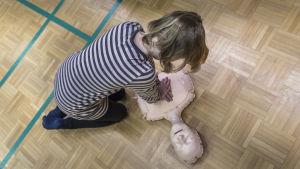 Lapsi opettelee elvyttämään.