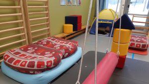 Lasten leikkihuone, jossa sänky, teltaa ja muita leikkivälineitä