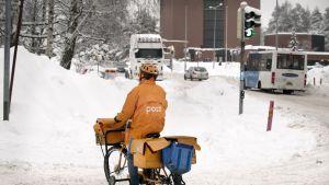 Postinjakaja ajaa polkupyörällä lumisessa katumaisemassa.