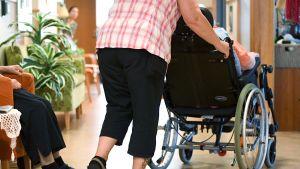 Hoitaja työntää pyörätuolissa istuvaa vanhusta