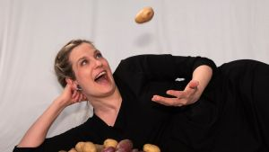 Tuulianna heittää perunaa ilmaan ja nauraa.