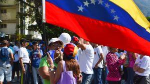 Mielenosoittajia ison Venezuelan lipun kanssa.