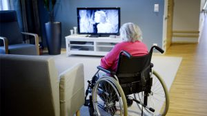 Vanhus pyörätuolissa katsoo televisiota.