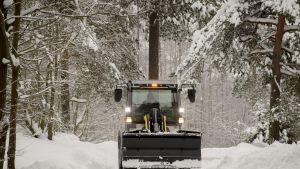 Lunta siirretään pos kävelytieltä pienellä traktorilla.