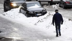 Jalankulkija etsii turvallista reittiä jäisellä pinnalla Helsingissä