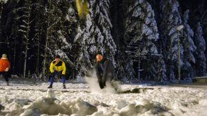 Ihmiset pelaa lentopalloa lumihangessa.