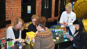 Aikuiset yliopistokeskuksen tutkijat leikkivät erilaisilla leluilla.