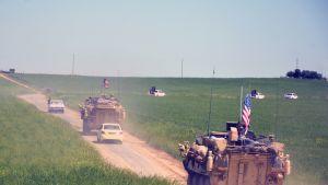 Kaksi Yhdysvaltojen panssarivaunua ja useita henkilöautoja kulkee poispäin tiellä.