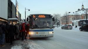 Ihmisiä nousemassa bussiin torin laidalla Kuopiossa.
