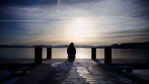 nainen laiturilla silhuettina, taustalla järvimaisema