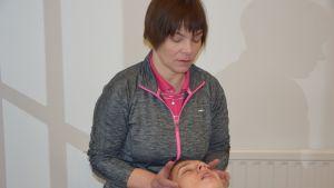 Nainen hieroo pitkällään olevan potilaan leukaa.