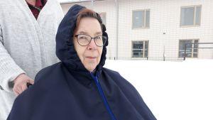 Mirja Malmi istuu pyörätuolissa hoitajansa ulkoiluttamana tummansininen ulkoiluviitta päällä.