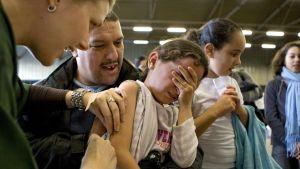 Kuvassa vasemmalla oleva hoitaja antaa rokotetta tytölle, joka on peittänyt silmänsä kädellään.