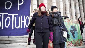 Heta-Elena Heiskanen (vas.) ja Elina Perttola osoittamassa mieltään perjantaiaamuna 8. helmikuuta.