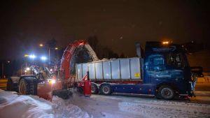 Suuri lumilinko suihkuttaa lunta kuorma-auton lavalle.