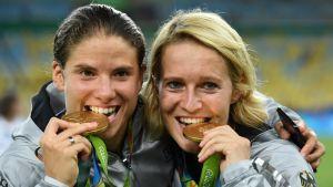 Saksalaisjalkapalloilijat Annike Krahn ja Saskia Bartusiak nautiskelivat kultamitaleistaan Rion olympialaisissa elokuussa 2016.