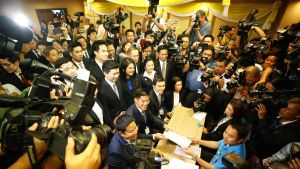 Thai Raksa -puolue luovuttaa vaaliasiakirjoja vaaliviranomaisille, ympärillä kymmeniä kuvaajia.