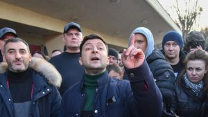 Volodymyr Zelensky puhuu etusormi pystyssä väkijoukon keskellä.