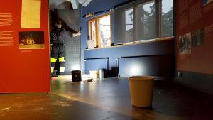 Ämpäreitä Kouvolan kaupunginmuseon näyttelytilan lattialla