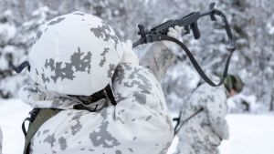 Varusmies huoltaa rynnäkkökivääriä talvisessa metsässä