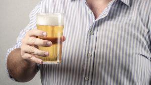 Miehellä on oluttuoppi kädessä.
