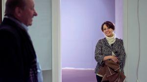 Nainen ja mies keskustelevat tyhjässä liiketilassa.