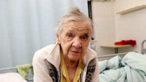 93-vuotias Hilja Volotinen istuu sairaalasängyllä.