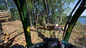 Metsäkone nostaa tukkeja pinoon.