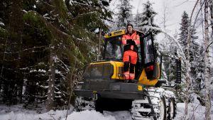 Metsäkoneen kuljettajaksi opiskeleva Juuso Lehtomäki seisoo kädet puuskassa ajokoneen ylätasanteella