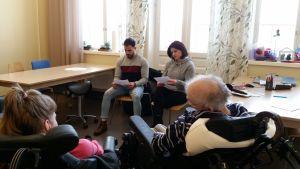 Kaksi ihmistä lukee ääneen, ja kaksi ihmistä istuu pyörätuolissa ja kuuntelee.