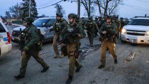 Raskaasti aseistettuja poliiseja ammuskelupaikalla Auroran kaupungissa Illinoisissa.