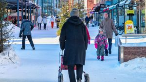 Rollaattoria käyttävä nainen Rovaniemen katuvilinässä talvipäivänä.
