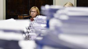 Perustuslakivaliokunnan puheenjohtaja Annika Lapintie paperipinojen takana.