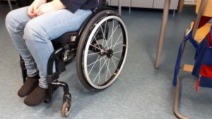 Pyörätuolissa istuu nainen